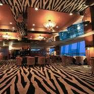 7席のカウンターと12卓のテーブル席、12名を収容できる個室席を用意する店内は、思わず気分が高揚してしまいそうな豪奢な雰囲気。白と黒のゼブラ柄のじゅうたんが、ラグジュアリーな気分を高めます。