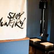 山口県下関市出身で書道家として活躍する「万美」が看板やエプロンの文字をデザインしています。店内にも同氏の作品が飾られ、和モダンの洗練された空間に躍動感を与えています。