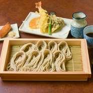 そば粉と布のりだけでつくるへぎそばは、のど越しが良く独特の歯応え。「へぎ」と呼ばれる器に小分けにして並べるのも特徴で、ワサビではなく和辛子をつけていただきます。海老と季節野菜の天麩羅、いなり寿司付き。