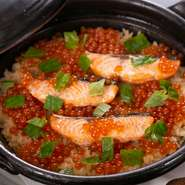 コース料理の〆には、旬食材たっぷりの炊き立ての土鍋ご飯が登場。写真は秋の一例の贅沢な『サケとイクラの炊き込みご飯』。冬は牡蠣、春は鯛、夏は夏野菜などが具材に。季節の滋味が薫るご飯に心がほぐれます。