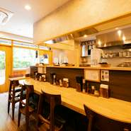 京王線初台駅から徒歩3分の玉川上水旧水路緑道沿いにある【麺屋 琥珀】は、洋楽R&Bが流れるおしゃれ空間でおいしいラーメンが楽しめるお店。緑道が望める心地よい店内で、こだわりの一杯を味わえます。