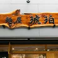 高樹齢杉に店主みずからがニスを塗って仕上げたという看板にも注目。さらに、店頭の丸看板などにあしらわれたロゴは、店主の義姉が切り絵で手作りしたものだとか。職人による一点ものの扉にもこだわりが光ります。