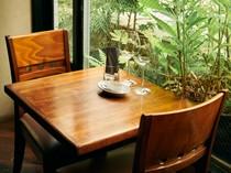 テーブル席の間合いも十分。シックな木のテーブルに緑が映える