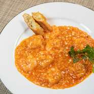 手作りのラー油と豆板醤の辛さと、海老油の香りがぷりぷりの海老に絡む人気メニュー。レモン汁でほどよい酸味をプラスしているのが特徴です。お皿には揚げパンを添えて。
