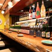 カウンターには酒瓶がずらり。国産サワーや日本酒が充実