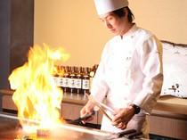 炎を巻き上げ調理を行う料理人