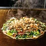豚肉、いか、小エビ、牛すじこんにゃくが入ったねぎ焼です。 九条ねぎをふんだんに使用し焼き上げました。 ソース味か特製しょうゆ味のどちらかお選びいただけます。 オススメはしょうゆ味です!!